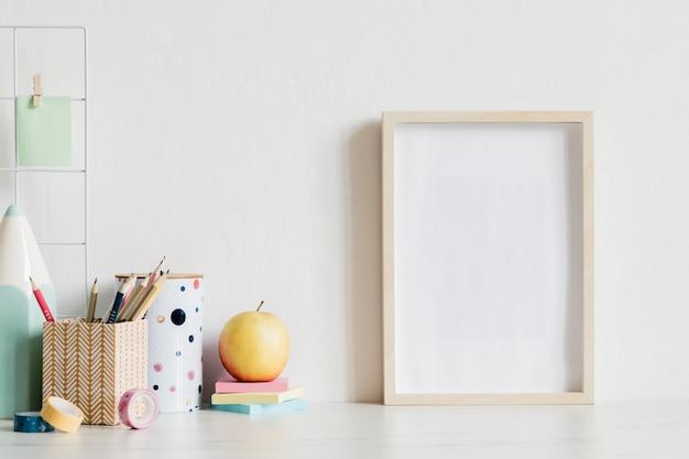 Interno dell'ufficio domestico scandinavo con cornice per poster in legno finto, accessori per ufficio di design, nastri, forniture, note, bastoncini per appunti, piante aeree. concetto minimalista. modello.