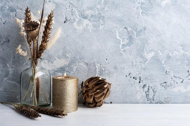 Interni scandinavi con fiori secchi dorati e candela accesa