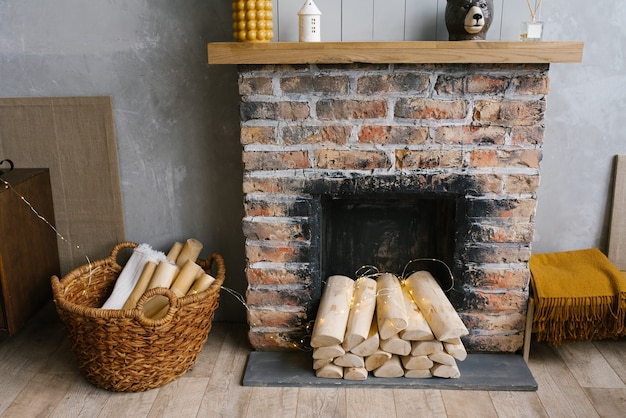 Interni scandinavi con camino in mattoni rossi, cesto di vimini per legna da ardere, pila di tronchi per un fuoco