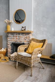 Un soggiorno scandinavo nei colori grigio e oro del 2021. l'interno di una casa di campagna con camino e sedia di vimini