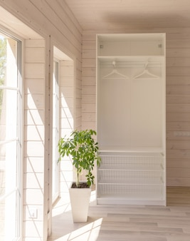 Appartamenti in stile scandinavo. interno luminoso della camera da letto in una casa in legno organico di colore bianco. mobili ikea, guardaroba. pavimento in legno, pareti, soffitto in legno. armadio bianco. finestre panoramiche.