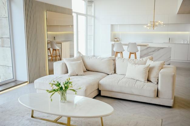 Luminosa sala da pranzo e cucina in stile scandinavo moderno e lussuoso con dettagli in legno, bianco, dettagli in marmo, nuovi mobili eleganti, comodo divano, design minimalista degli interni nordici.