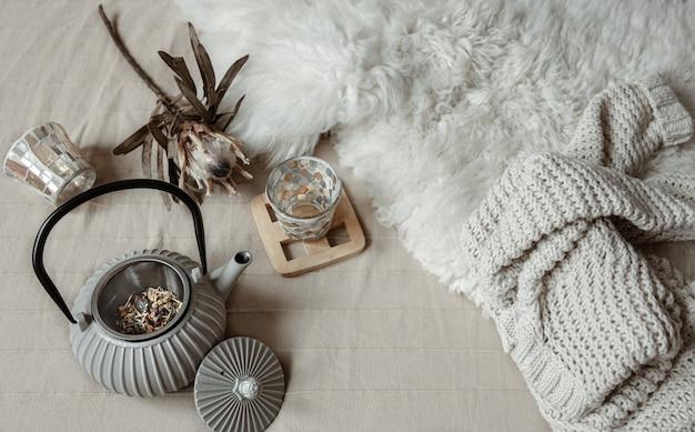 Teiera in stile scandinavo con tè lavorato a maglia e dettagli decorativi vista dall'alto.
