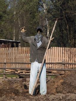 Spaventapasseri in giardino a braccia aperte e un bastone.
