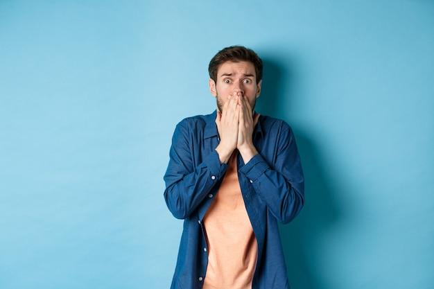 Uomo ansioso spaventato che copre la bocca con le mani e guardando qualcosa di terrificante, in piedi su sfondo blu. Foto Premium