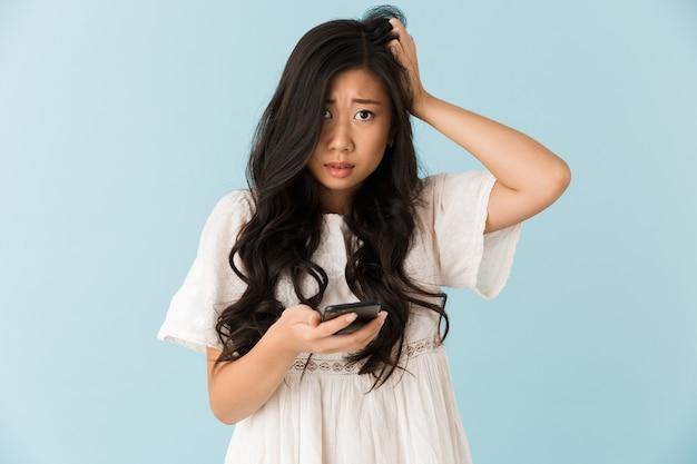 Bella donna asiatica spaventata isolata sopra la parete blu facendo uso del telefono cellulare