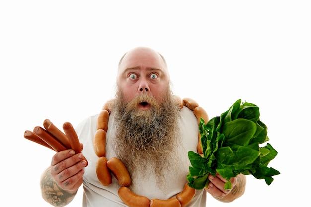 Un uomo barbuto spaventato che indossava una brusca di salsicce intorno al collo mostra salsicce e verdure alla telecamera ed esprimeva paura e sorpresa