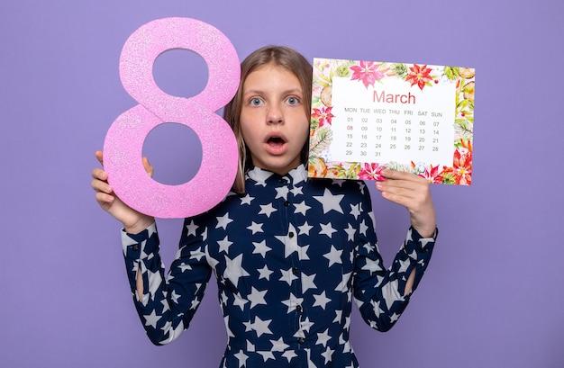 Bella bambina spaventata sulla felice festa della donna che tiene il calendario con il numero otto intorno al viso