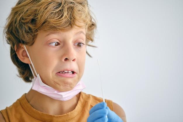 Ragazzo spaventato con infermiera durante il test covid in clinica
