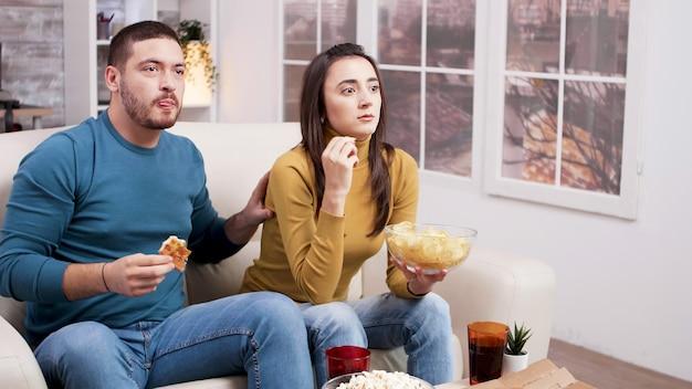 Coppia spaventata dopo un momento spaventoso nel film dalla tv. coppia seduta sul divano a mangiare la pizza.