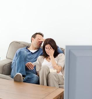 Coppia spaventata che nasconde i loro volti mentre si guarda un film dell'orrore