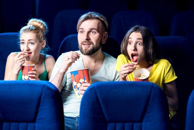 Amici spaventati che guardano film seduti insieme a popcorn al cinema