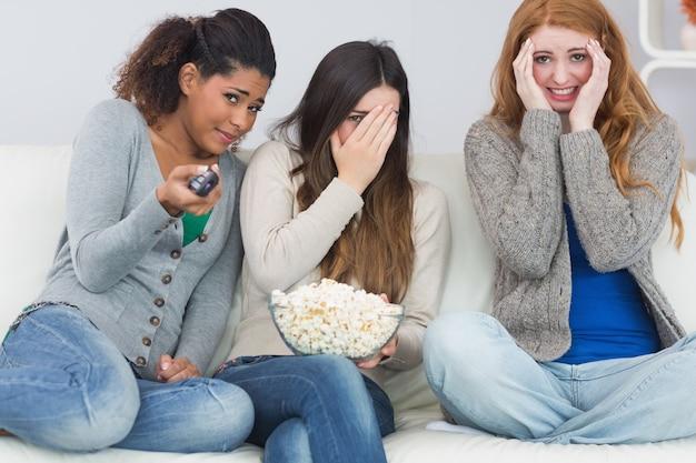 Amici spaventati con telecomando e ciotola di popcorn sul divano