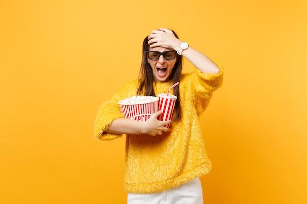 Donna frustrata spaventata con gli occhi chiusi in occhiali imax 3d che urla aggrappandosi alla testa guardando film che tiene in mano una tazza di popcorn di soda isolata su sfondo giallo. persone sincere emozioni nel cinema.