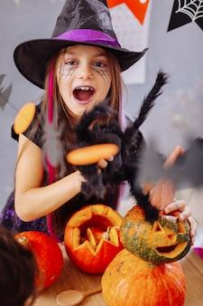 Ragazza spaventata. bella ragazza carina e divertente dagli occhi scuri con labbra viola che si sente spaventata guardando le decorazioni di halloween