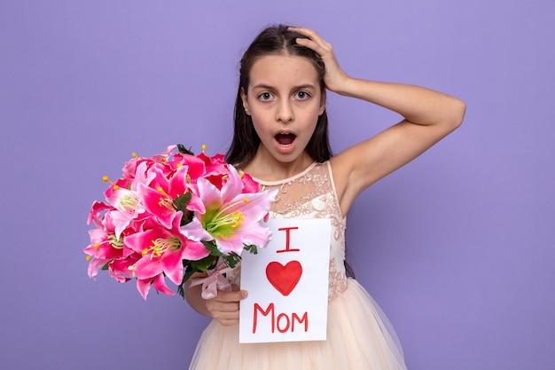 Bella bambina spaventata afferrò la testa durante la festa della donna felice con un mazzo di fiori con un biglietto di auguri