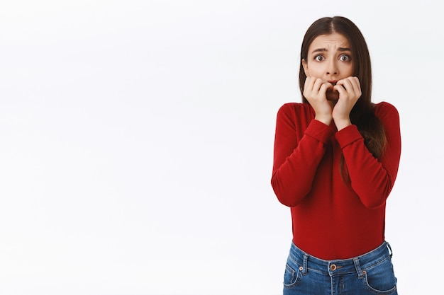 Spaventata giovane ragazza timida innocente in maglione rosso, sentendosi spaventata e senza parole dalla paura, mangiarsi le unghie, fissare la telecamera stupita dall'espressione della vittima, inorridita, terrorizzata dal film horror