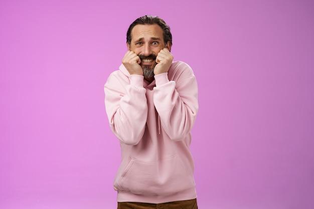 Spaventato insicuro sciocco adulto uomo barbuto capelli grigi in felpa con cappuccio rosa premere palmi bocca morso dita serrare i denti scioccato spaventato spalancare gli occhi terrorizzato in piedi stupore inorridito, sfondo viola.