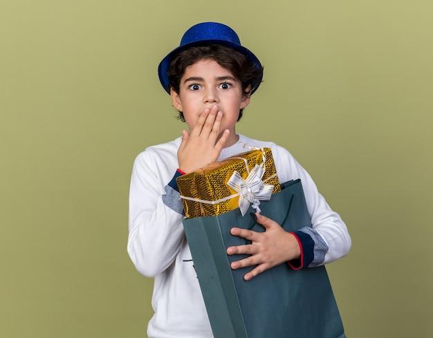 Un ragazzino spaventato che indossa un cappello da festa blu che tiene in mano una borsa regalo ha coperto la bocca con la mano isolata sul muro verde oliva