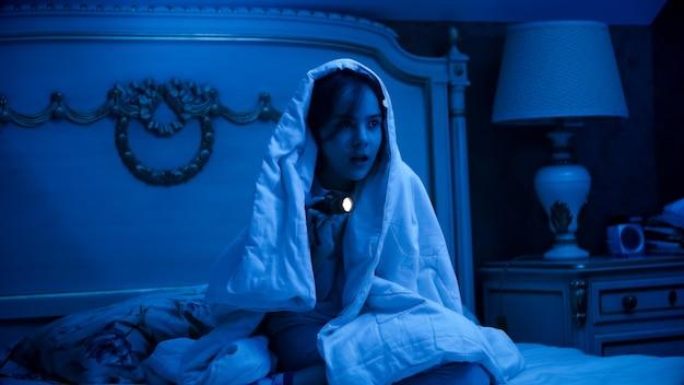 Bambina spaventata che si nasconde sotto la coperta di notte e cerca mostri.