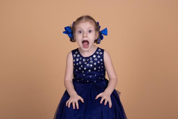 Bambina spaventata con la bocca aperta e gli occhi, stupita, scioccata sorpresa, emozioni facciali