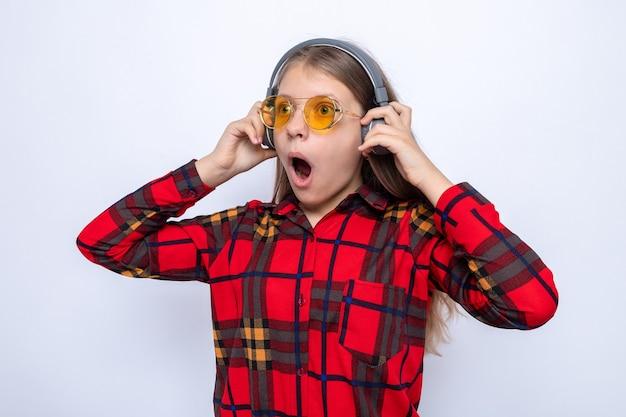 Bella bambina spaventata che indossa una maglietta rossa e occhiali con le cuffie isolate sul muro bianco