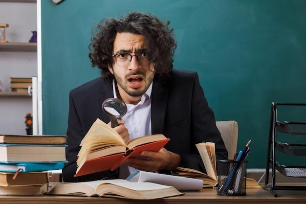 Insegnante maschio spaventato con gli occhiali che tiene in mano un libro con lente di ingrandimento seduto al tavolo con strumenti scolastici in classe