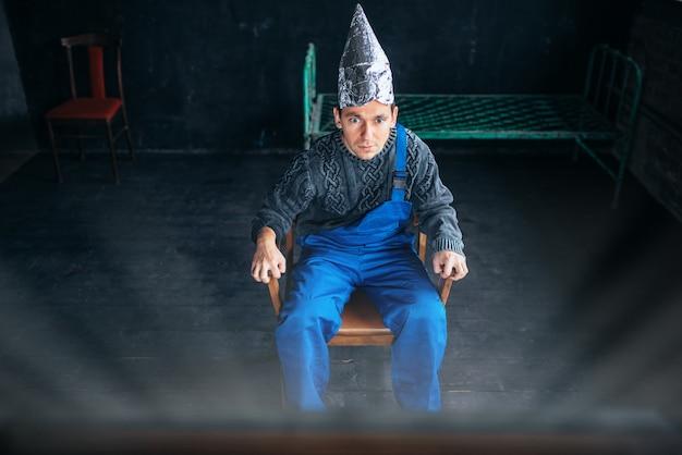 Uomo spaventato in cappello di lamina di alluminio si siede sulla sedia e guarda la tv, concetto di paranoia. ufo, teoria del complotto, protezione dal furto di cervello, fobia