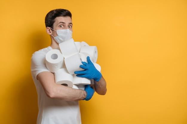 Uomo spaventato con maschera protettiva contro il virus covid-19 tiene tra le mani molti rotoli di carta igienica