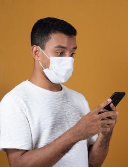 Uomo spaventato in maglietta bianca che indossa la maschera con il cellulare nelle sue mani