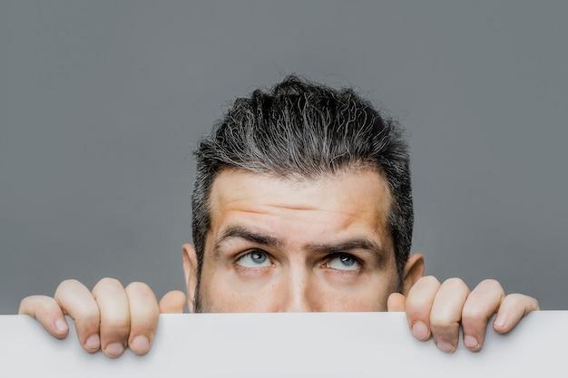 Uomo spaventato con carta giovane uomo barbuto che punta sullo sfondo blu allo spazio della copia