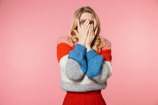 Una giovane donna piuttosto bella e nervosa spaventata in posa isolata su un muro rosa