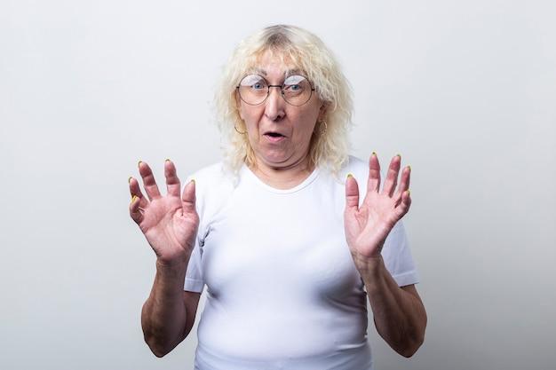 Donna anziana spaventata con gli occhiali che prova paura su sfondo chiaro.