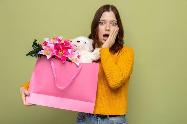 Spaventata di mettere la mano sulla guancia bella ragazza che tiene in mano una borsa regalo