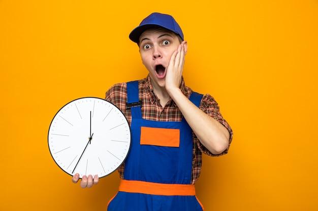 Paura di mettere la mano sulla guancia giovane addetto alle pulizie che indossa l'uniforme e il berretto tiene l'orologio da parete