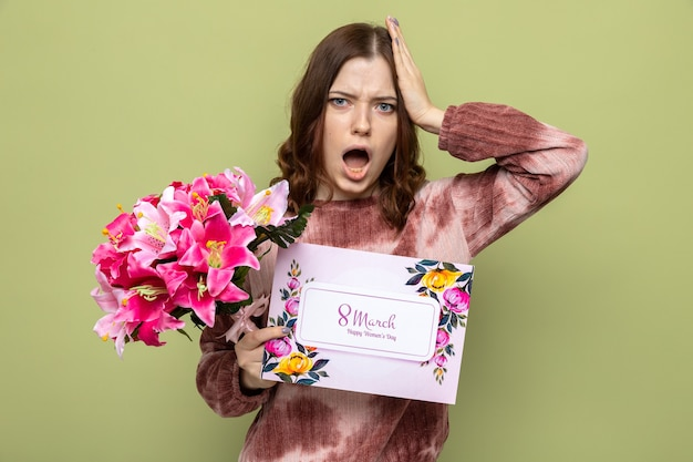 Spaventata mettendo la mano sulla testa bella ragazza in felice festa della donna che tiene bouquet con biglietto di auguri
