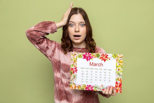 Spaventata mettendo la mano sulla testa bella ragazza il giorno delle donne felici tenendo il calendario