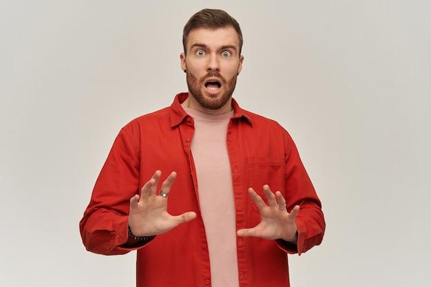 Giovane sconvolto spaventato in camicia rossa con la barba che difende dalle minacce con le mani e che grida sopra il muro bianco