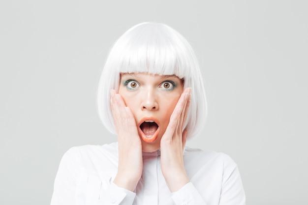 Giovane donna scioccata spaventata con la bocca aperta e le mani sulle guance