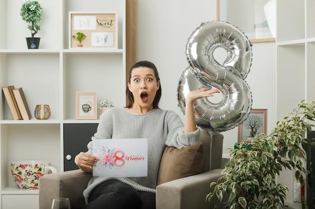 Spaventata mano allargata bella donna il giorno delle donne felici con in mano una cartolina seduta sulla poltrona in soggiorno