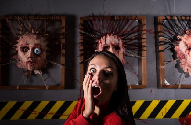 Donna spaventata di fronte a facce scorticate per la spaventosa scena del crimine del terrore a tema halloween