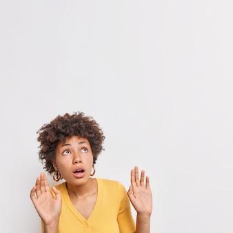 La donna spaventata sussulta dalla paura tiene i palmi alzati si previene dal pericolo guarda sopra l'oggetto invisibile che cade su di lei frustrato da qualcosa isolato sul muro bianco