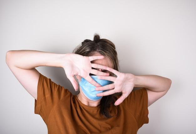 La donna spaventata nella mascherina medica copre il viso con le mani, isolate