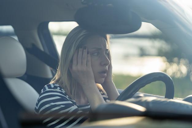 La donna spaventata si siede al sedile del conducente in macchina ha paura di guidare un veicolo di guida femminile ansioso di mezza età