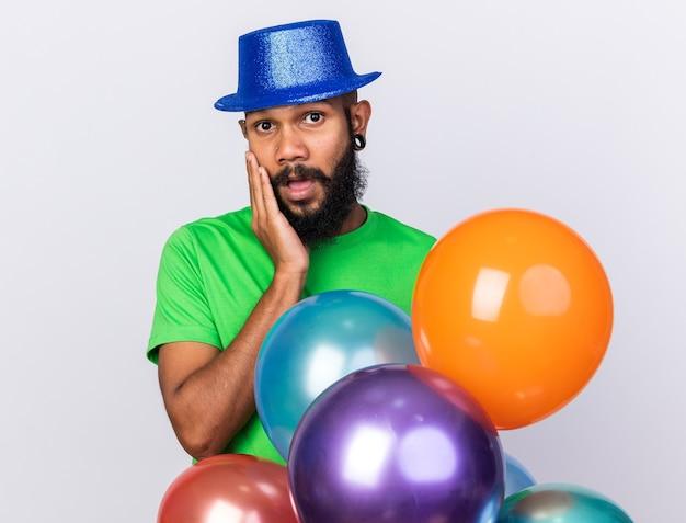 Giovane ragazzo afroamericano spaventato che indossa un cappello da festa in piedi dietro i palloncini mettendo la mano sulla guancia isolata sul muro bianco