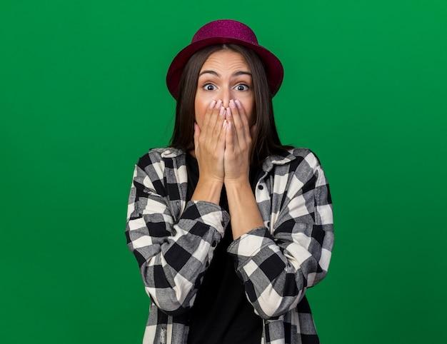 La giovane bella ragazza spaventata che indossa il cappello del partito ha coperto la bocca di mano isolata sulla parete verde