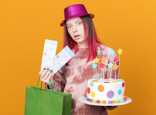 Spaventata giovane bella ragazza che indossa cappello da festa tenendo la torta con sacchetto regalo e biglietti isolati su parete arancione