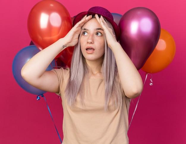 Giovane bella ragazza spaventata che indossa un cappello da festa in piedi di fronte a palloncini che mettono le mani sulla testa di cavallo isolata sul muro rosa
