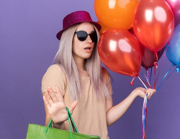 Giovane bella ragazza spaventata che indossa un cappello da festa con occhiali che tengono palloncini con un sacchetto regalo che mostra il gesto di arresto