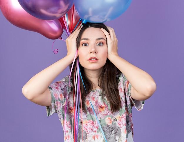 La giovane bella donna spaventata che indossa il cappello del partito che tiene i palloni ha afferrato la testa isolata sulla parete blu